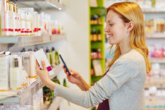 Woman scanning barcode in a drugstore. Young smiling woman scanning barcode with smartphone in a drugstore royalty free stock image