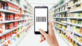 Woman scanning a barcode with her phone. Woman doing grocery shopping at the supermarket and scanning a barcode using her smartphone, technology and retail royalty free stock photo