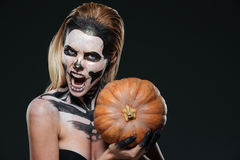 Woman with scared gothic makeup holding pumpkin and shouting stock image