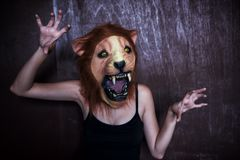 Woman with Halloween lion mask. Woman with scared lion mask on dark wooden background. Haloween fantasy dress concept royalty free stock photo
