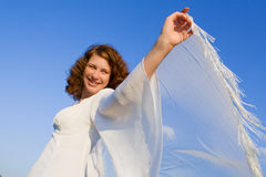 Woman and scarf. Joyful young woman against a background blue sky Royalty Free Stock Image