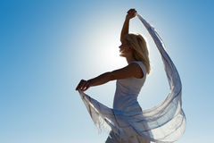 Woman with scarf feeling balanced. Woman with white scarf being backlit by the sun standing in the wind feeling happy and balanced Royalty Free Stock Images
