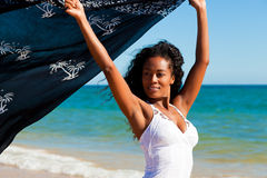 Woman with scarf feeling balanced. Woman with black scarf standing in the wind on a beach feeling happy and balanced Stock Image