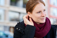 Woman with a Scarf Fixing Her Hair Stock Photo