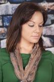 Woman scarf green shirt brick wall look down royalty free stock photos
