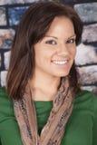 Woman scarf green shirt brick wall smile stock image