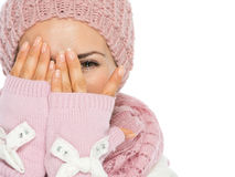 Woman in scarf and hat hiding behind hand. Woman in knit scarf, hat and mittens hiding behind hands Royalty Free Stock Photography
