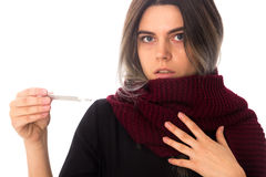 Woman in scarf holding a thermometer. Young woman in black shirt with vinous long scarf holding a thermometer and looking at it on white background in studio Royalty Free Stock Images