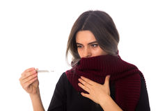 Woman in scarf holding a thermometer. Young woman in black shirt with vinous scarf holding a thermometer and looking at it on white background in studio Stock Image