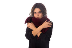 Woman in scarf hugging herself. Young woman in black blouse with long vinous scarf holding hugging herself on white background in studio Royalty Free Stock Images
