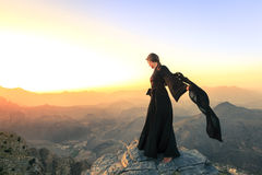 Woman with a scarf in the mountains. Lone woman in abaya in Al Hajar Mountains of Oman at sunset Stock Photography