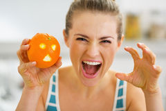 Woman scaring with orange with hallowing face. Young woman scaring with orange with hallowing face Stock Images
