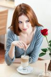 Woman with scarlet rose at the cafe Stock Image