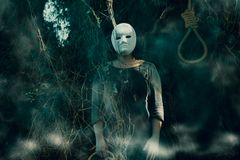 Woman with a scary mask. Portrait of a woman in the forest with a scary mask on her face and a rope in her hand royalty free stock image