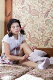 Woman in schoolgirl adjusts her sock stock photo
