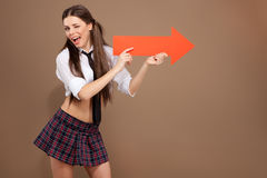 Woman in a schoolgirl costume holding an arrow sign Stock Photography