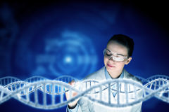 Woman science technologist in laboratory. Woman scientist examining DNA molecule image at media screen Stock Image