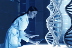 Woman science technologist in laboratory. Woman scientist examining DNA molecule image at media screen Stock Photos