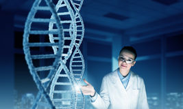Woman science technologist in laboratory. Woman scientist examining DNA molecule image at media screen Royalty Free Stock Images