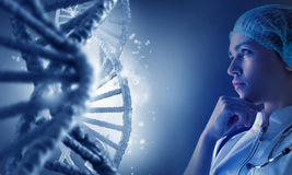 Woman science technologist in laboratory. Woman scientist looking thoughtfully at DNA molecule image at media screen Royalty Free Stock Photography