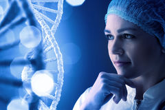 Woman science technologist in laboratory. Woman scientist looking thoughtfully at DNA molecule image at media screen Royalty Free Stock Images