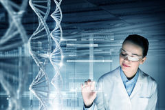 Woman science technologist in laboratory. Woman scientist touching DNA molecule image at media screen Royalty Free Stock Photography