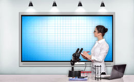 Woman scientific researcher looking on tv screen Royalty Free Stock Photos