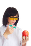 Woman scientist. Injecting chemicals into apple on white Royalty Free Stock Photos