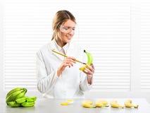 Woman scientist coloring bananas; artificial color stock photos