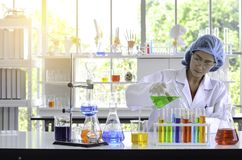 The woman scientist doing experiment in laboratory that have flare light. stock photo