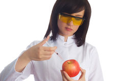 Woman scientist injecting chemicals. Into apple on white Royalty Free Stock Photos