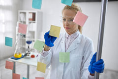 Woman scientist in laboratory write chemical formula Stock Images