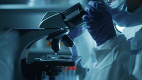 A woman scientist is looking into microscope, biochemical research. Scientific and medical lab instrument. A doctor is