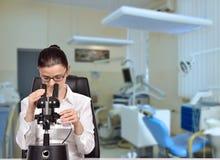 Woman scientist looking through microscope Stock Photos