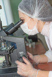 Woman scientist looking in a microscope Royalty Free Stock Images