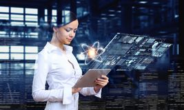 Woman scientist making research. Mixed media. Attractive woman in science laboratory working with tablet pc. Mixed media Royalty Free Stock Photography