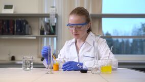 Woman scientist mixing thickening fluids and liquid. Spbas analyzing scientific research.