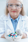 Woman scientist in protective gloves holding pills in hands in lab Stock Image
