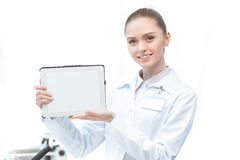 Woman scientist showing digital tablet with blank screen royalty free stock photography