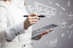 Woman scientist or student working with various high school maths and science formula. Woman scientist or student working with various high school maths and Royalty Free Stock Images