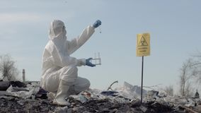 Woman scientist in uniform and protective gloves holding test tubes taking sample of garbage from the big dirty dump stock video footage
