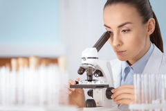 Woman scientist working with microscope in laboratory Royalty Free Stock Images