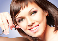 Woman with scissors. Attractive smiling girl with scissors, cutting her hair Royalty Free Stock Photography