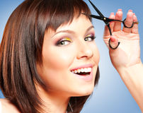 Woman with scissors. Attractive smiling girl with scissors, cutting her hair Stock Image