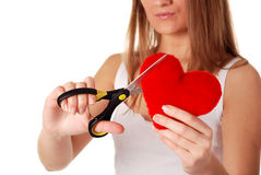 Woman with scissors and red heart. Young beatiful woman cutting with scissors red heart Royalty Free Stock Image
