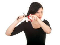 Woman with a scissors trying to cut her hair Royalty Free Stock Image