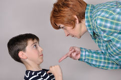 Woman scolding a scared young boy Royalty Free Stock Image
