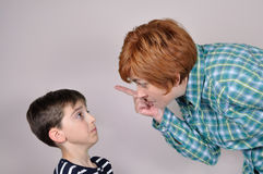 Woman scolding a scared young boy stock images
