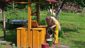 Woman scoop water from rural yellow painted well in bucket stock video
