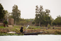 Woman scooping water out of a canoe in Mali Stock Image